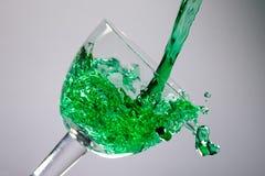 绿色液体puring对玻璃 免版税库存照片