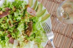 绿色混合生菜盘用鲕梨、熏火腿、葡萄干和胡桃在竹席子 免版税图库摄影