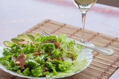 绿色混合生菜盘用鲕梨、熏火腿、葡萄干和胡桃在竹席子 免版税库存图片