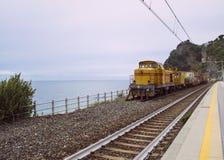 黄色火车在海洋前面停放了在Corniglia,意大利 免版税库存图片