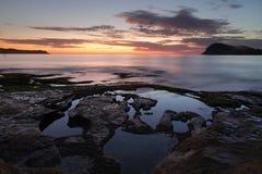 从绿色点珍珠海滩的黎明天空 库存图片