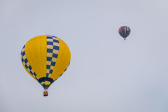 黄色热空气气球通过天空公平地漂浮在黄昏在沃伦县农夫` s,和谐,新泽西, 8/1/17的 库存照片