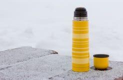 黄色热水瓶和杯子 库存图片