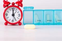 黄色片剂和医学时间背景 免版税库存照片