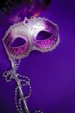 紫色狂欢节或威尼斯式面具在紫色背景 免版税库存图片