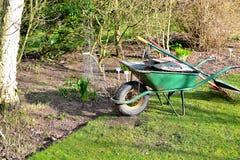 绿色独轮车在庭院里 免版税库存照片