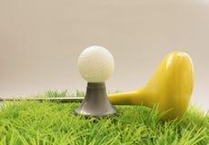 黄色玩具轻击棒和高尔夫球在草 免版税库存照片