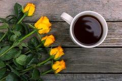 黄色玫瑰和白色咖啡花束在木背景的 被仿造的强光 免版税图库摄影