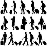 黑色现出轮廓带着手提箱的旅客  免版税库存图片
