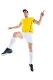 黄色球衣踢的足球运动员 库存图片