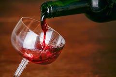从绿色瓶的倾吐的红葡萄酒到典雅的玻璃里 库存图片