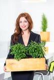 绿色生活 拿着有植物的可爱的年轻女实业家一个箱子隔绝在白色背景 环境 免版税库存照片