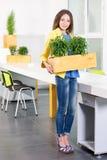 绿色生活 站立在现代顶楼办公室的可爱的年轻女实业家拿着有植物的一个箱子 环境 免版税库存照片
