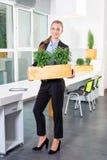 绿色生活 站立在现代顶楼办公室的可爱的年轻女实业家拿着有植物的一个箱子 环境 免版税库存图片