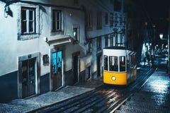 黄色电车在夜城市布局的里斯本 免版税库存照片