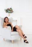 黑色的一名华美的妇女是松弛在一把白色扶手椅子 库存图片