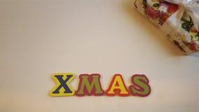 色的信件清楚地说明在白色帆布的Xmas与圣诞节礼物 库存照片
