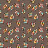 色的叶子的无缝的样式在布朗背景的 免版税库存照片