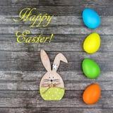 复活节彩蛋和兔宝宝在木背景 免版税库存图片