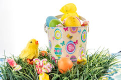 色的复活节彩蛋、小鸡、糖果和桶在草 免版税库存照片