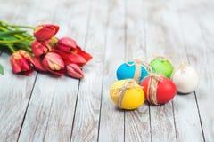 色的复活节彩蛋、花盆有绿草的和美丽的郁金香在木背景 库存照片