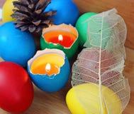 色的复活节彩蛋,蜡烛,火焰 免版税库存照片