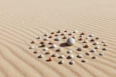 色的小卵石的样式以一个圈子的形式在干净的沙子 免版税库存照片