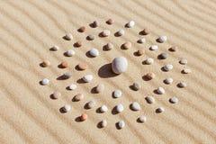 色的小卵石的样式以一个圈子的形式在干净的沙子 免版税图库摄影