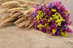 色的干燥花束和和麦子的干燥耳朵在土气黄麻bac的 免版税图库摄影