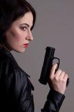 黑色的性感的妇女与在灰色的枪 免版税图库摄影