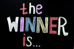 色的手书面文本`优胜者是在黑板的` 免版税库存照片