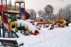 色的操场在冬天,神色放弃了在雪下 免版税库存照片