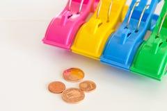 色的晒衣夹和硬币 免版税库存照片