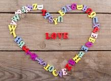 色的木信件框架在心脏形状的和文本& x22; Love& x22; 库存照片