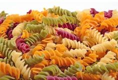 色的未煮过的意大利面团fusilli堆在白色的 库存照片