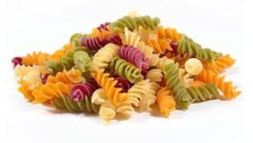 色的未煮过的意大利面团fusilli堆在白色的 免版税库存图片