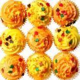 色的杯形蛋糕与黄色和橙色结霜和洒。背景。甜食物为万圣夜 免版税库存照片