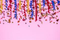 色的欢乐丝带和五彩纸屑边界在桃红色背景 免版税库存图片