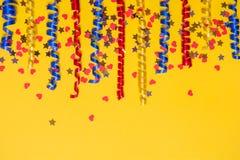 色的欢乐丝带和五彩纸屑边界在黄色背景 礼物风景 免版税库存照片