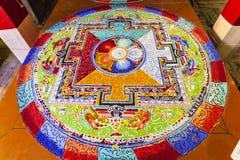 从色的沙子的西藏坛场掀动 免版税库存照片