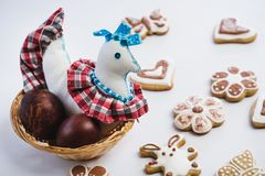 色的玩具鸡和被绘的鸡复活节彩蛋在柳条巢和姜饼曲奇饼,盖用白色和巧克力ici 免版税库存图片