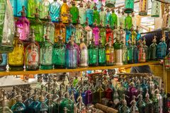 色的玻璃古色古香的苏打瓶行在一旧货市场排队了在圣特尔莫,布宜诺斯艾利斯,阿根廷 库存图片