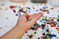色的玻璃马赛克片断在儿童` s手上在桌上 创造性和学会 免版税库存图片