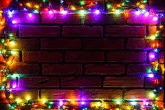 色的电灯泡花圈和诗歌选  与光和大方的本体空间的圣诞节背景 圣诞灯边界 免版税图库摄影