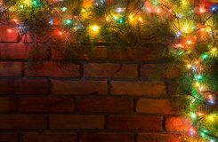 色的电灯泡花圈和诗歌选  抽象空白背景圣诞节黑暗的装饰设计模式红色的星形 库存照片