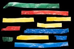 色的磁带小条在黑背景的更低的三的 免版税库存图片