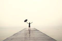 黑色的端庄的妇女高兴与他们的胳膊在雨中 免版税库存照片