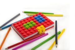 色的笔记本和铅笔在白色背景 库存照片