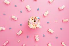 色的糖果和蛋白软糖与热奶咖啡杯子在桃红色背景 平的位置,顶视图 彩虹在杯子的甘蔗用咖啡 免版税图库摄影