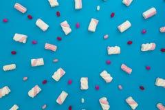 色的糖果和蛋白软糖在蓝色背景 平的位置,顶视图 库存图片